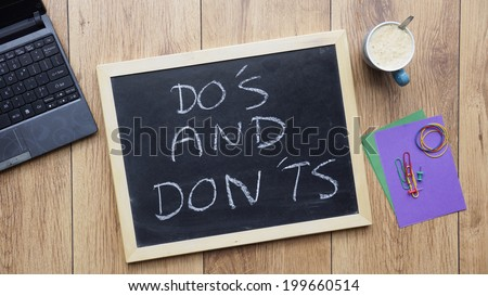 Do's and don'ts written on a chalkboard at the office - stock photo