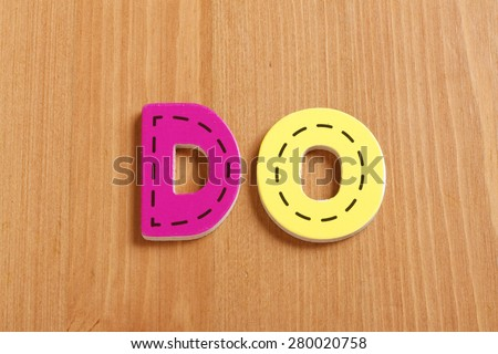DO, spell by woody puzzle letters with woody background - stock photo