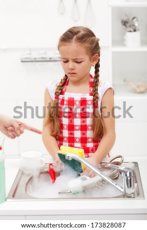 Do the dishes this instant - sad and grumpy little girl ordered to wash up tableware
