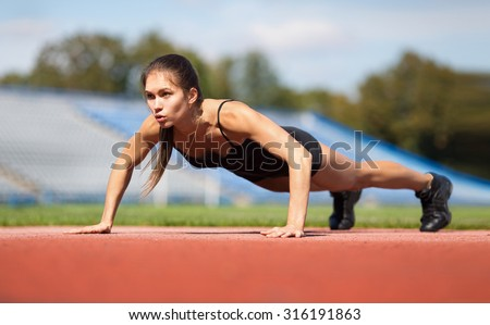 do the squeezing.warming-up.young beauty girl do exercises at the stadium