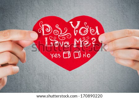 Do you love me? Valentine's day background. Closeup of female hands holding red heart with sign - stock photo