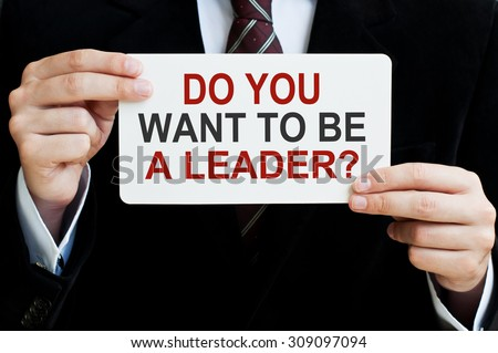 Do You Want to be a Leader? Businessman holding a card with a message text written on it.