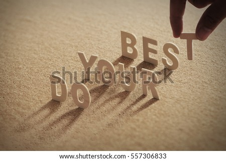 DO YOUR BEST wood word on compressed or cork board with human's finger at T letter.