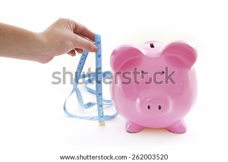 Do Your Savings Measure Up?  Piggy Bank on White Background being measured - stock photo