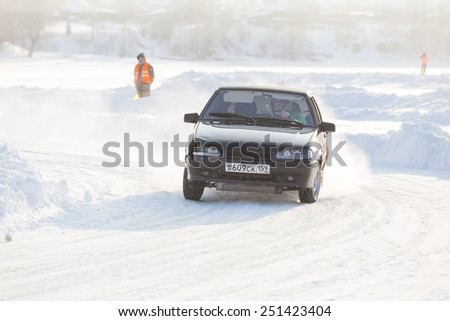 Dobryanka, Russia - February 7, 2015. Urban ice race. Lada car VAZ-2114 comes in turn to snow sports track - stock photo