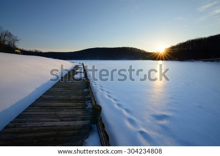 Dock and Frozen Lake at Sunset - stock photo