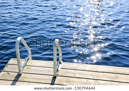 Dock and ladder on calm summer lake with sparkling water in Ontario Canada - stock photo
