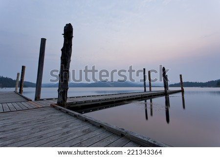 Dock and lake at sunrise on the calm Chatcolet Lake in north Idaho. - stock photo