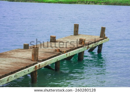 Dock/Jetty to a tropical beach in the sun day - stock photo
