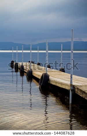 dock on lake on cloudy sunset - stock photo