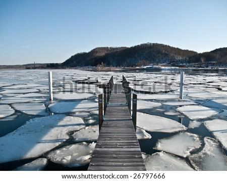 Dock on semi frozen lake - stock photo