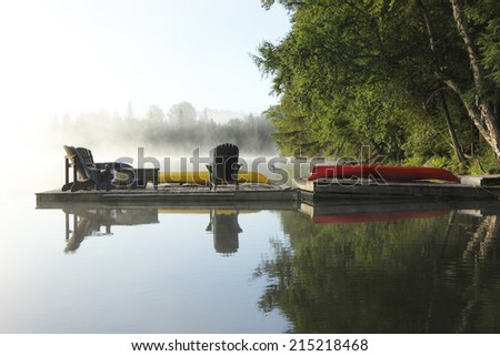 Dock with Chairs, Canoe and Kayak on a Misty Morning - Haliburton, Ontario, Canada - stock photo
