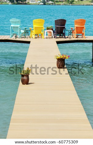 dock with colorful Adirondack chairs - stock photo