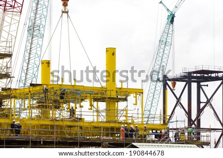 Dock workers constructing an (offshore) oil platform - stock photo