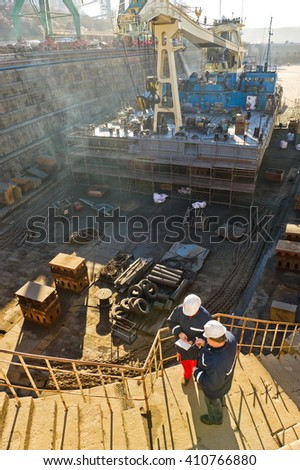 Dock workers in dry dock. - stock photo