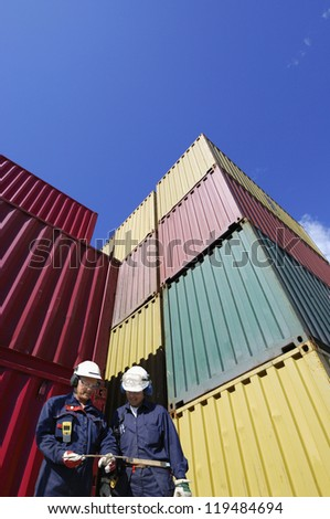 dock workers with stacks of shipping containers - stock photo