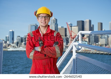 Docker and deck hand posing on the bridge of a ship, about to moor off in a city harbor, with the seattle skyline in the background - stock photo