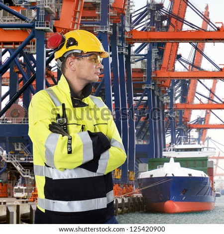 Docker, wearing a hard hat, gloves, safety glasses and a chemical resistant coat, sternly overlooking  an industrial harbor with large cranes, unloading containers from a freight ship - stock photo