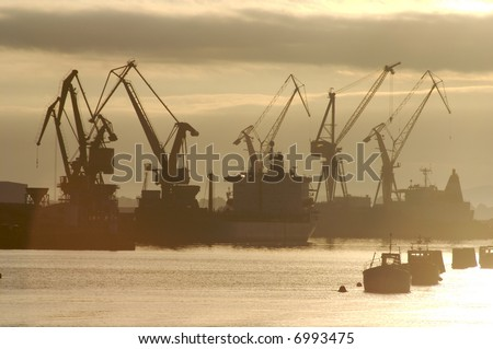 Dockside tower cranes in the early sunrise mist