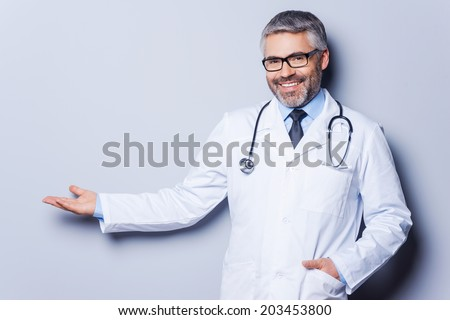 Doctor advertising your product. Cheerful mature doctor looking at camera and pointing away while standing against grey background - stock photo