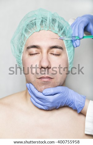 Doctor aesthetician makes hyaluronic acid beauty injections in the forehead of male patient with closed eyes in a medical cap and white t-shirt - stock photo