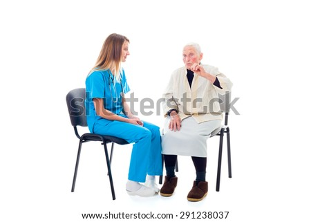 Doctor and elderly patient sitting on chairs and talking.
