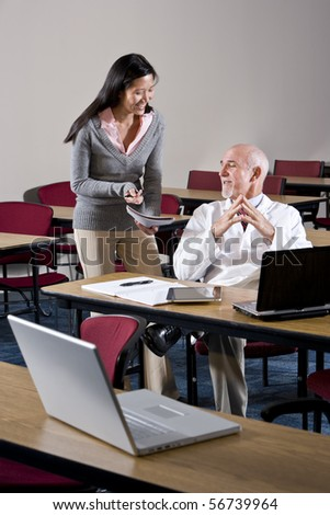 Doctor and female assistant in conference room looking at notebook - stock photo