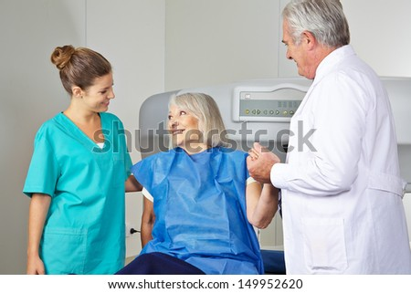 Doctor and MTA helping senior woman in radiology at bone density measurement - stock photo