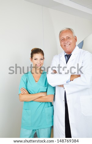 Doctor and nurse as a team with arms crossed in a hospital - stock photo