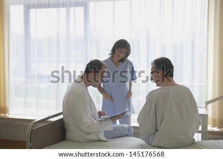 Doctor and nurse communicating with patient in hospital room - stock photo