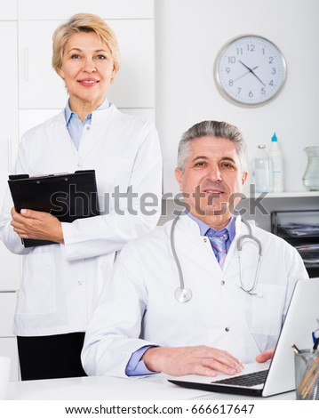 Doctor and nurse in white medical gown waiting for visit patients at table