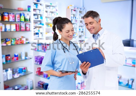 Doctor and nurse looking at clipboard against pharmacist with grey hair standing behind shelves of drugs - stock photo