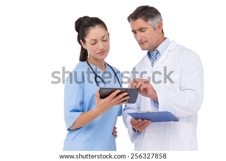 Doctor and nurse looking at clipboard on white background - stock photo