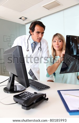 Doctor and nurse looking at Xray - stock photo