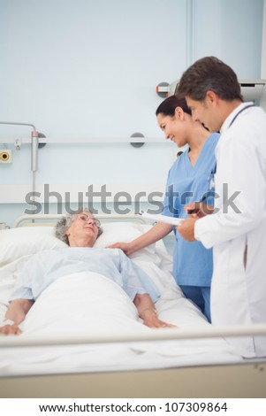 Doctor and nurse speaking to a patient in hospital ward - stock photo
