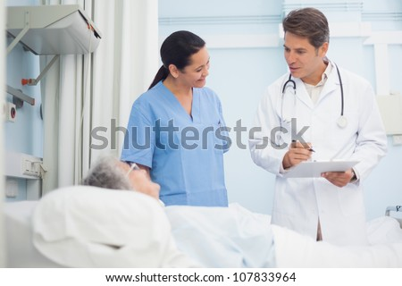Doctor and nurse talking to a patient in hospital ward - stock photo