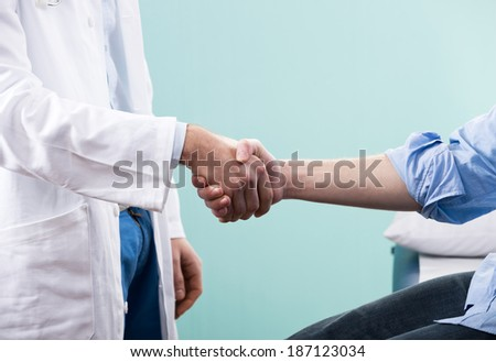 Doctor and patient handshake close-up at the clinic.