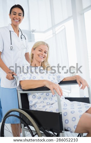 Doctor and patient in wheelchair smiling at camera in hospital - stock photo