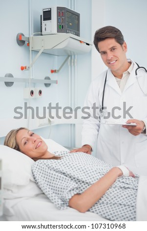 Doctor and patient smiling in hospital ward - stock photo