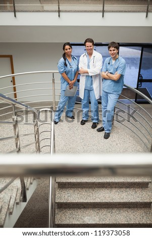 Doctor and two nurse standing on the stairs smiling at the camera