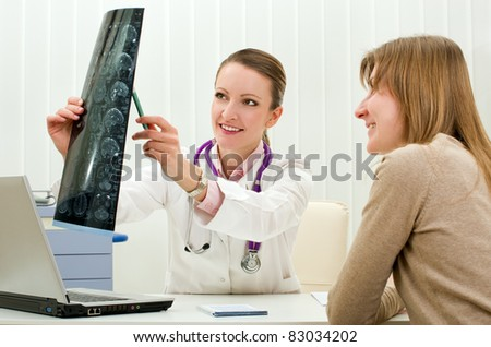 Doctor and woman patient looking x-ray scan - stock photo