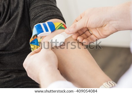Doctor Applying Bandage On Patient's Hand After Blood Test - stock photo