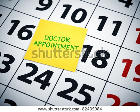 Doctor appointment written on a sticky note on a calendar. - stock photo