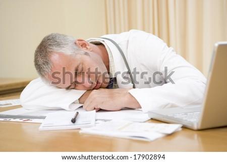 Doctor asleep on desk - stock photo