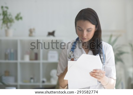 Doctor at her medical office using mobile phone and holding papers. View through the glass - stock photo