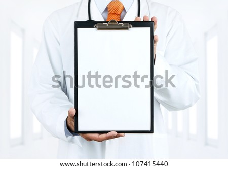 Doctor at hospital holding blank clipboard with copy space - stock photo