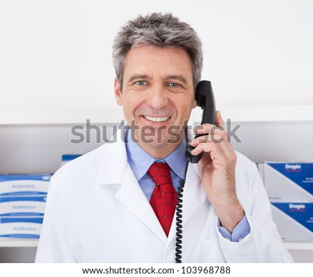 Doctor at the drugstore calling on the phone - stock photo