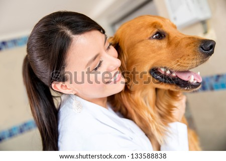 Doctor at the vet hugging a beautiful dog - stock photo