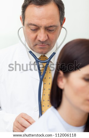Doctor auscultating a patient in an examination - stock photo