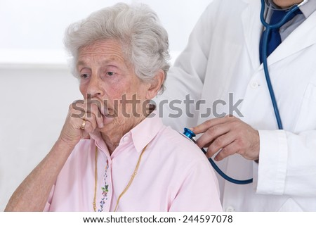 Doctor auscultating senior patient's lungs